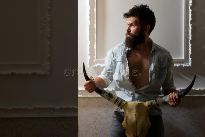 Зверский бородатый человек с животным черепом серьезный хипстер с бородой мужской парикмахер E зверский кавказец стоковое фото rf