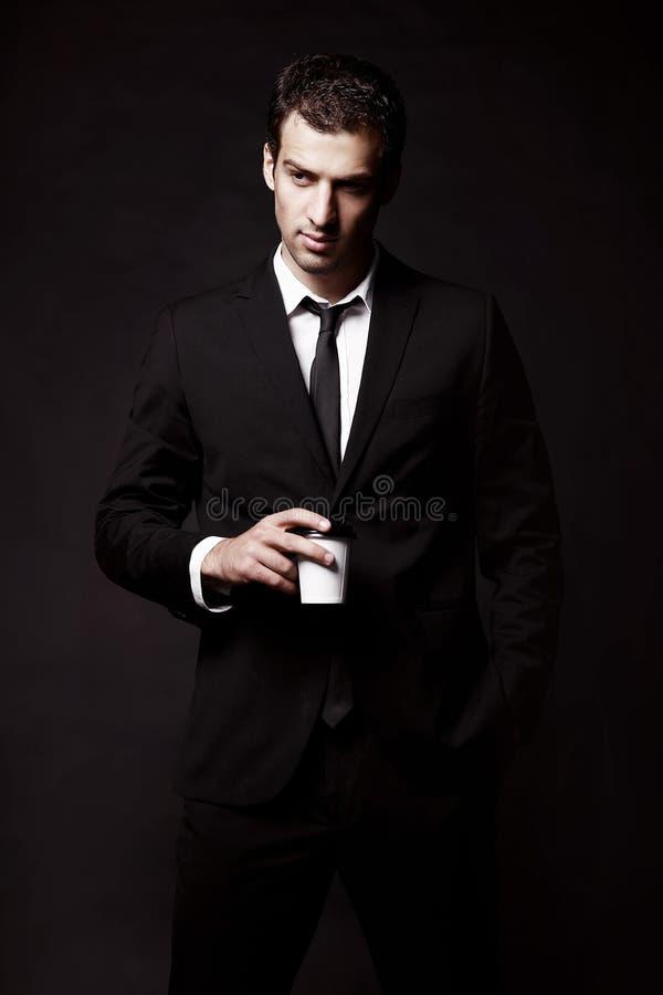 Зверский парень в черном костюме с кофе Черная предпосылка стоковая фотография