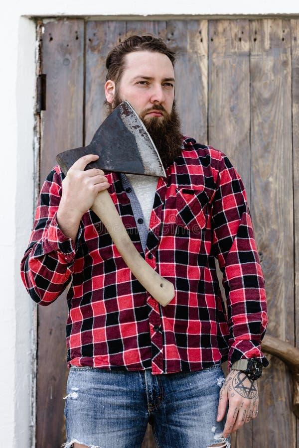 Зверский сильный человек с бородой одетой в проверенной рубашке и сорванных джинсах стоя с осью в руках против стоковые фотографии rf