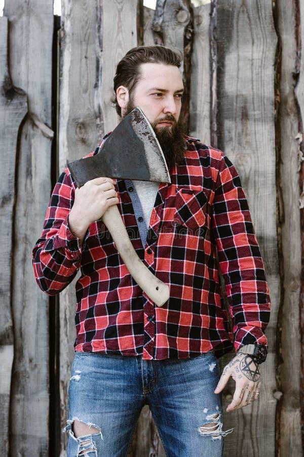 Зверский сильный человек с бородой одетой в проверенной рубашке и сорванных джинсах стоя с осью в руках против стоковое изображение rf