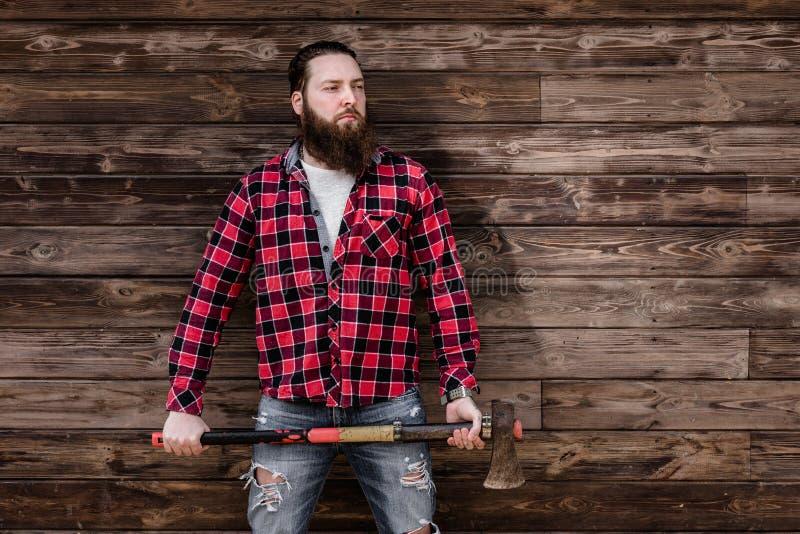 Зверский сильный человек с бородой одетой в проверенной рубашке и сорванных стойках джинсов с осью в руках на стоковое фото