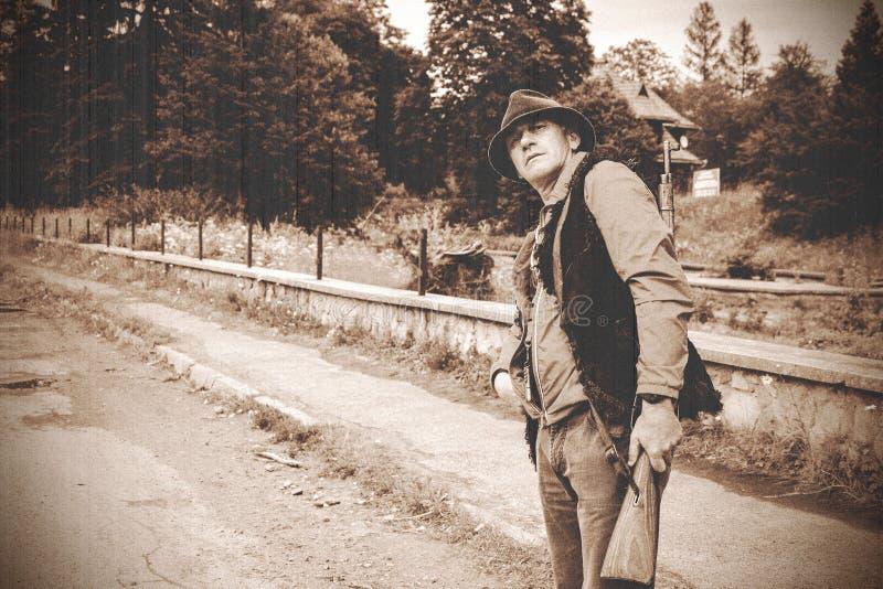 Зверский человек с винтовкой на его плечах в украинских Карпатах стоковое изображение