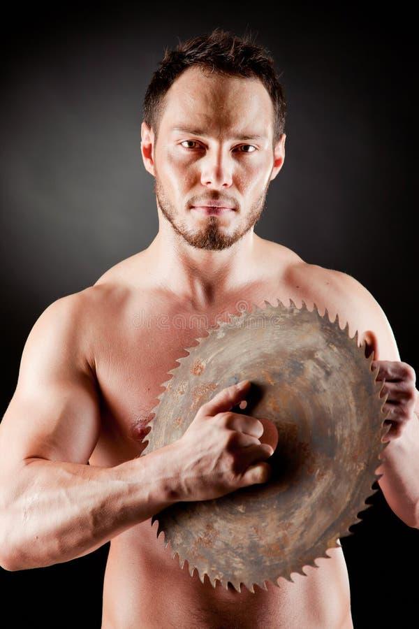 Зверский человек держа круговое лезвие стоковое изображение