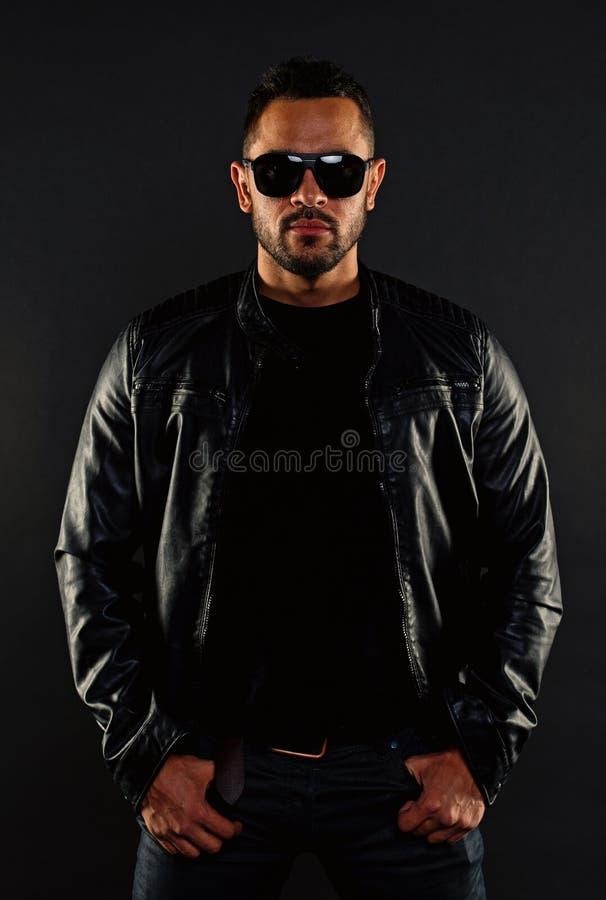 Зверское мачо в кожаной куртке Бородатый человек в солнечных очках моды Сексуальность и привлекательность людей Фотомодель внутри стоковая фотография rf