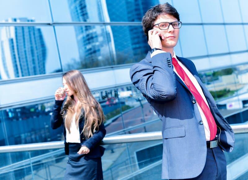 Звонить по телефону младшего администратора динамический вне его офиса стоковое изображение rf