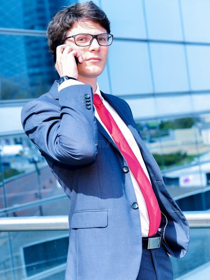 Звонить по телефону младшего администратора динамический вне его офиса стоковые фотографии rf
