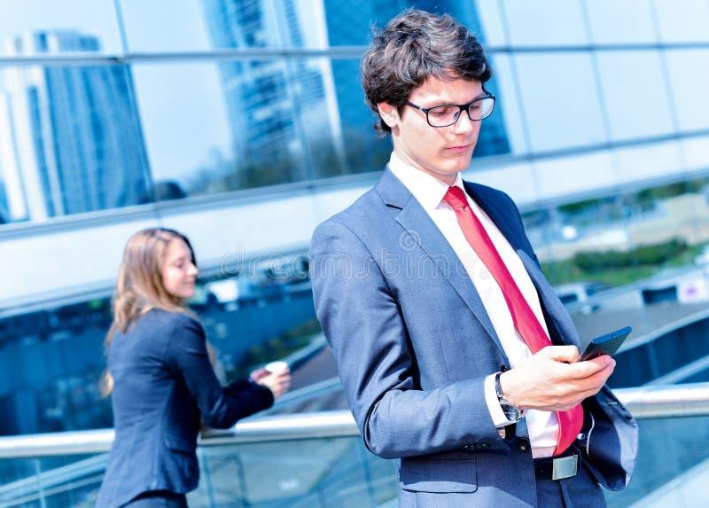 Звонить по телефону младшего администратора динамический вне его офиса стоковые изображения
