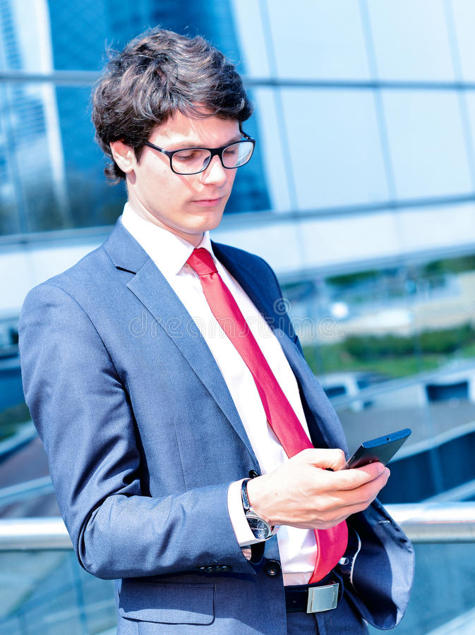 Звонить по телефону младшего администратора динамический вне его офиса стоковая фотография