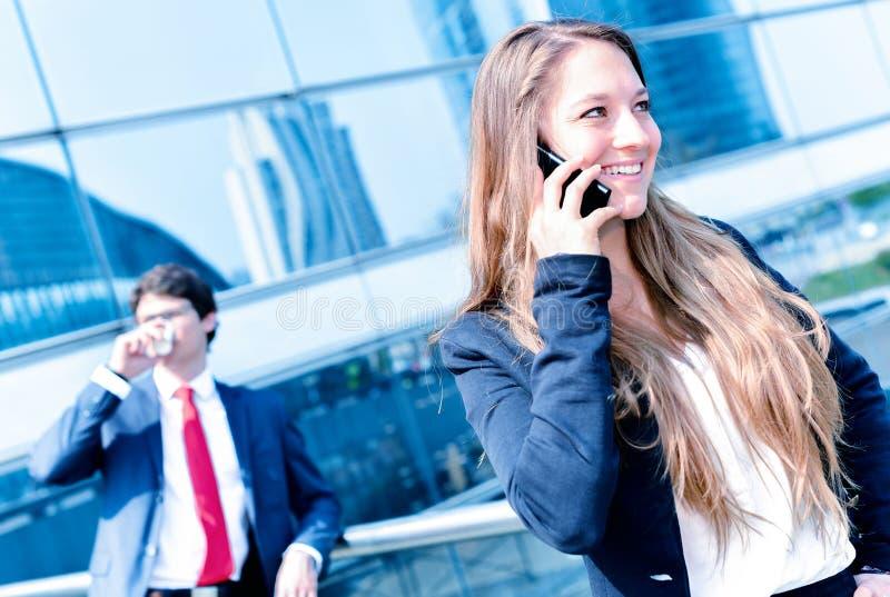 Звонить по телефону младшего администратора динамический снаружи ее офиса стоковая фотография rf