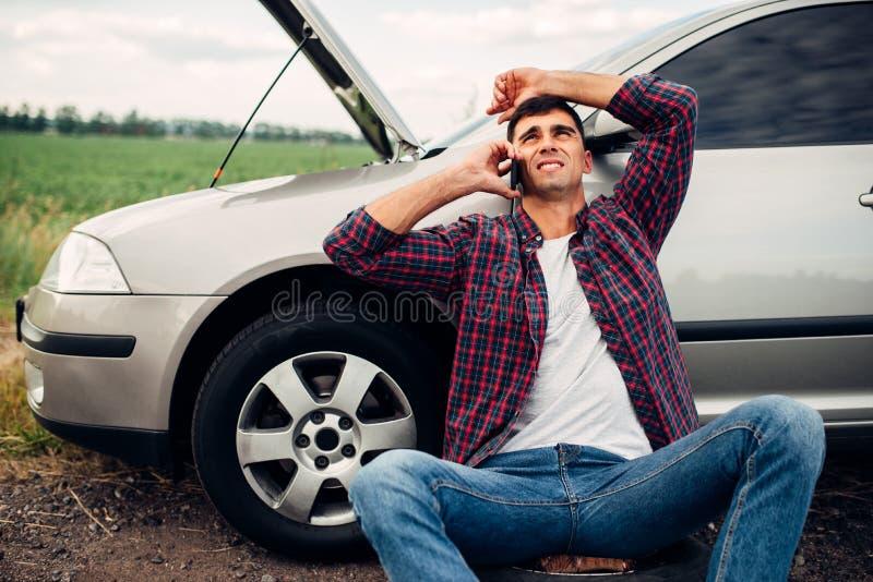 Звонки человека к чрезвычайному обслуживани, сломанному автомобилю стоковая фотография rf