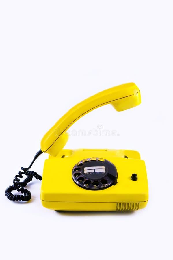 Звонок ответа телефона старого стиля 90 предпосылки disko ретро винтажной телефонной трубки телефона желтый пластиковый белый под стоковое изображение