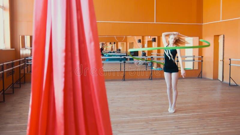 Звукомерная гимнастика - молодая женщина тренируя тренировку гимнастики с зеленой лентой стоковые фото