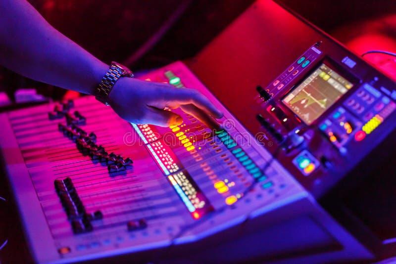Звукооператор работая с консолью музыки ядрового equiplment- концерта аудио смешивая с подсвеченными кнопками стоковая фотография