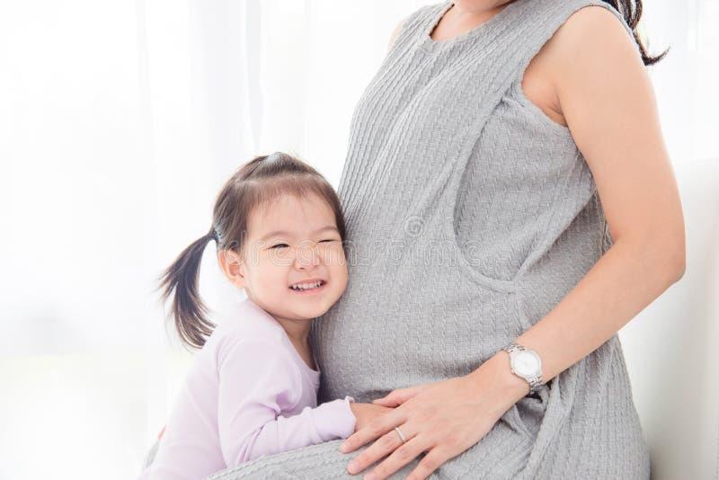 Звук девушки слушая от ее беременного живота ` s матери стоковое фото