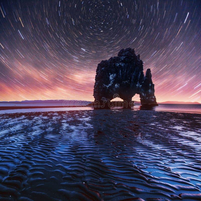 Звёздное небо в эффектном утесе в море на северном побережье Исландии Сказания говорят что окаменелый troll стоковые изображения