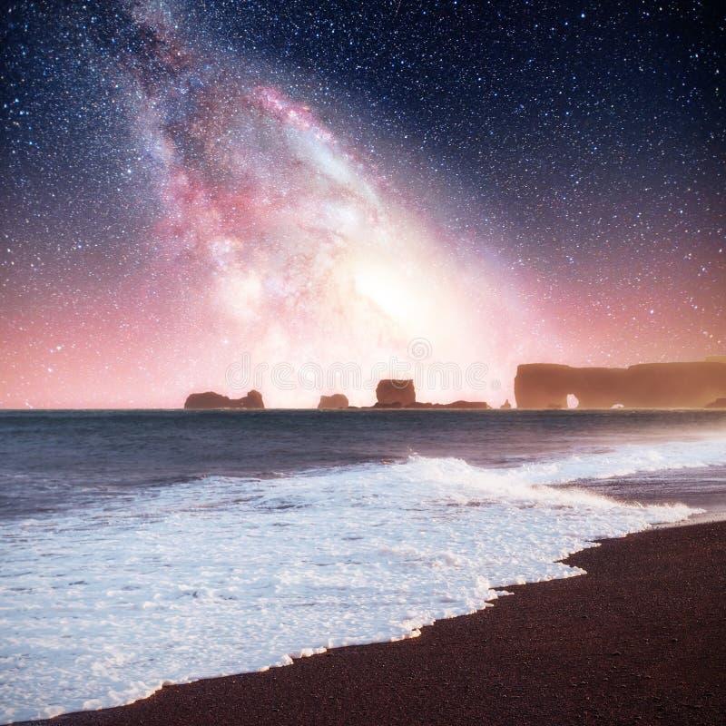 Звёздное небо в эффектном утесе в море на северном побережье Исландии Сказания говорят что окаменелый troll стоковые фото
