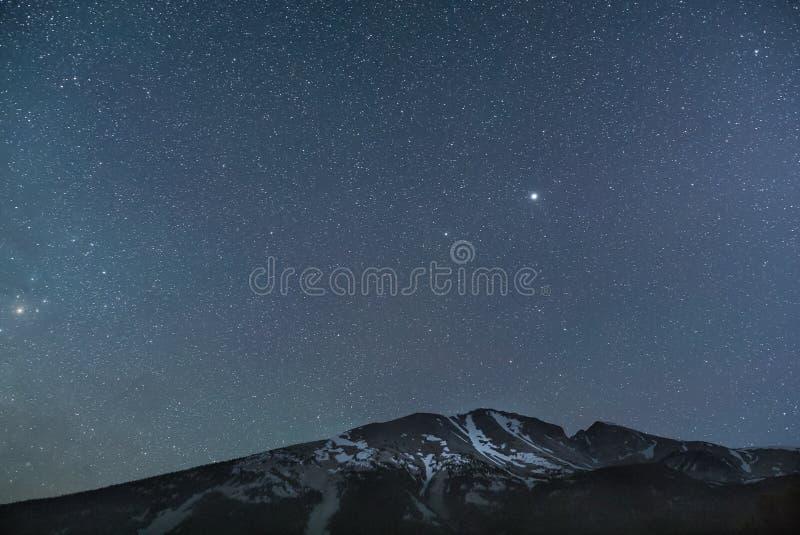 Звёздное небо над снежной горой стоковые фото