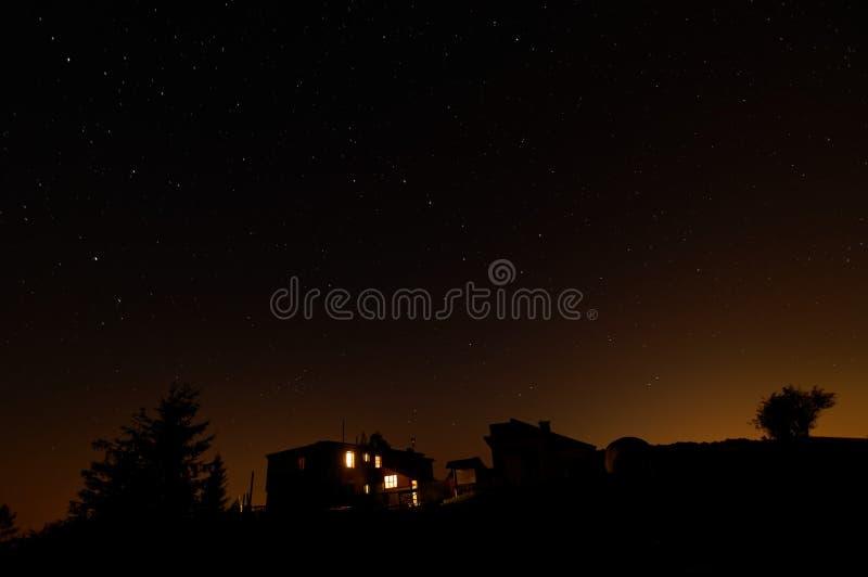 Звёздное небо na górze горы с укрытием и шатрами Света в окне и оранжевом зареве стоковые изображения