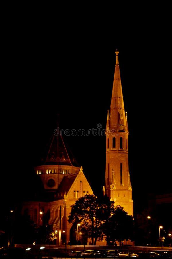 Здание высоко-шпиля на крыше накаляет желтым вечером город ночи высокая часовня стоковая фотография