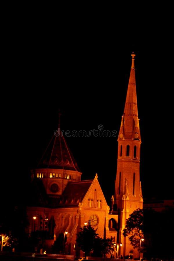 Здание высоко-шпиля на крыше накаляет желтым вечером город ночи высокая часовня стоковое изображение rf