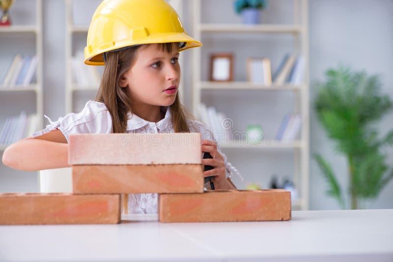 Здание маленькой девочки с кирпичами конструкции стоковое изображение rf