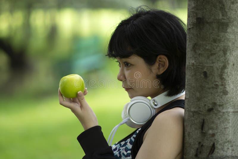 Здоровая азиатка с зеленым яблоком стоковые фото