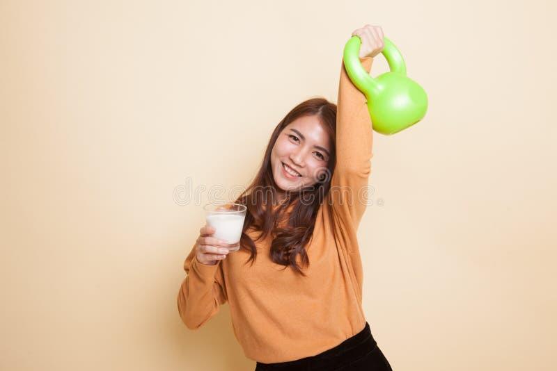Здоровая азиатская женщина выпивая стекло молока и гантели стоковая фотография