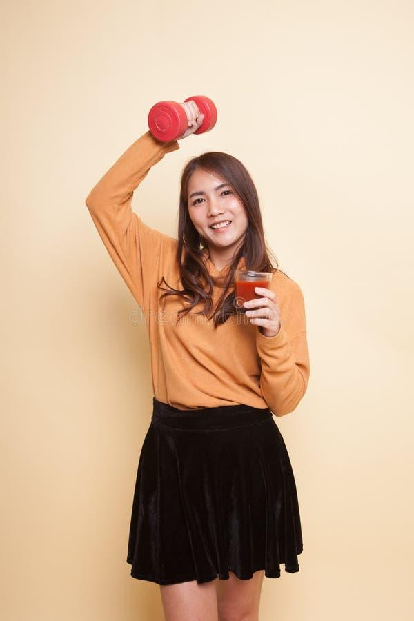 Здоровая азиатская женщина с гантелью и соком томата стоковое фото