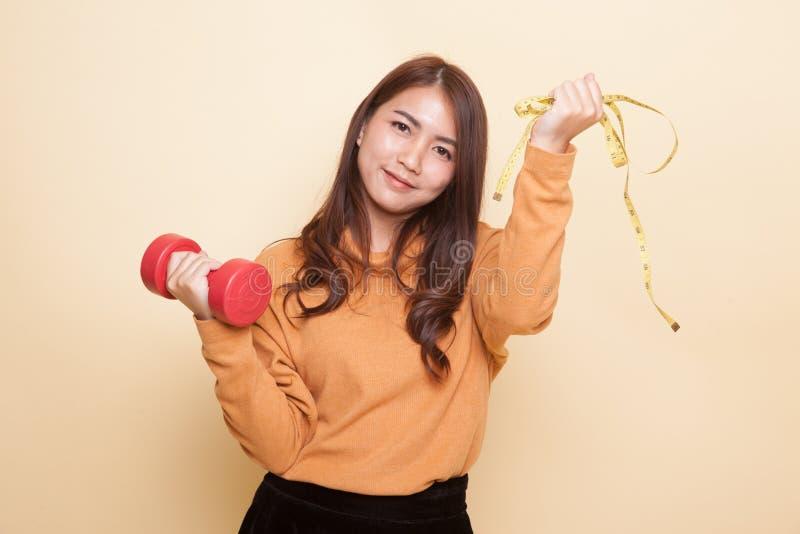 Здоровая азиатская женщина с гантелями и измеряя лентой стоковая фотография rf