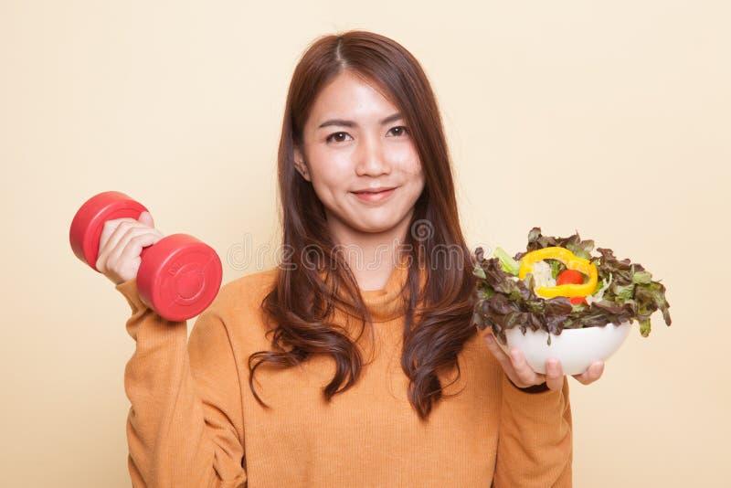 Здоровая азиатская женщина с гантелями и салатом стоковое фото rf