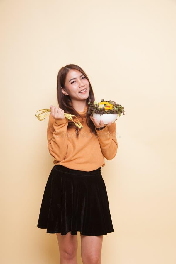 Здоровая азиатская женщина с измеряя лентой и салатом стоковая фотография