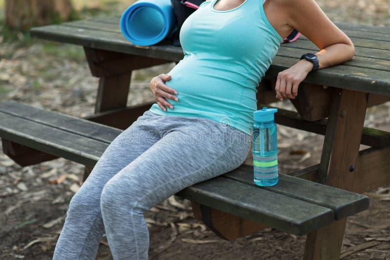 Здоровая беременная женщина фитнеса принимая остатки разминки стоковые изображения