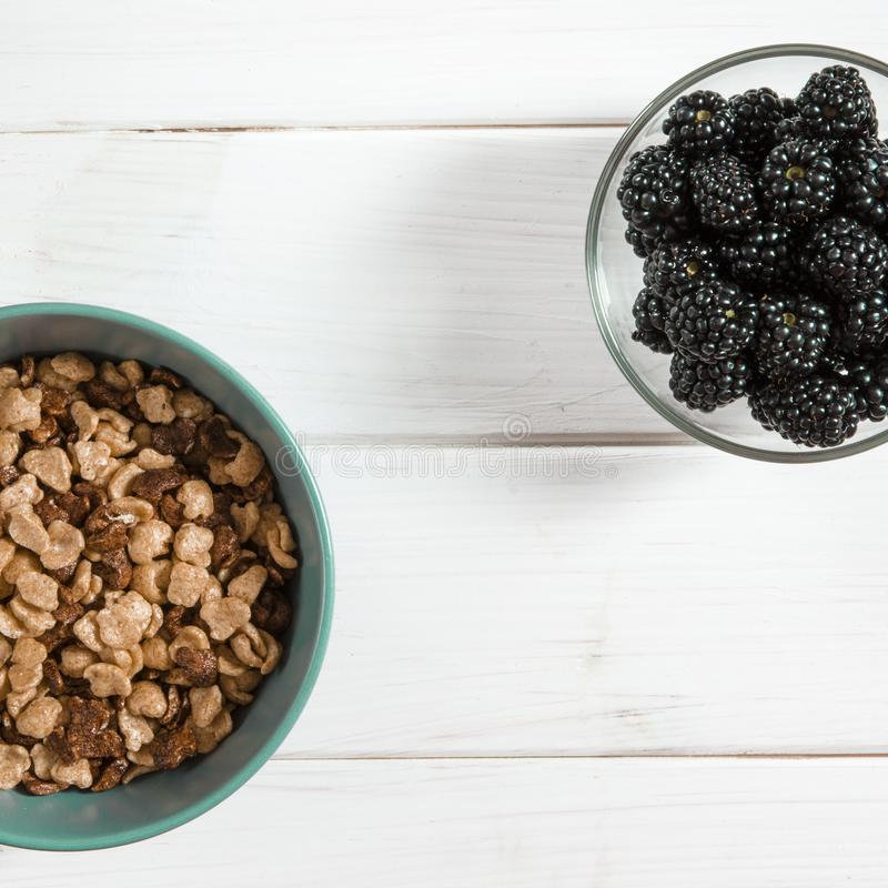 Здоровая еда: здоровый завтрак корнфлексов и ягод ежевики на белой таблице дерева стоковые изображения rf