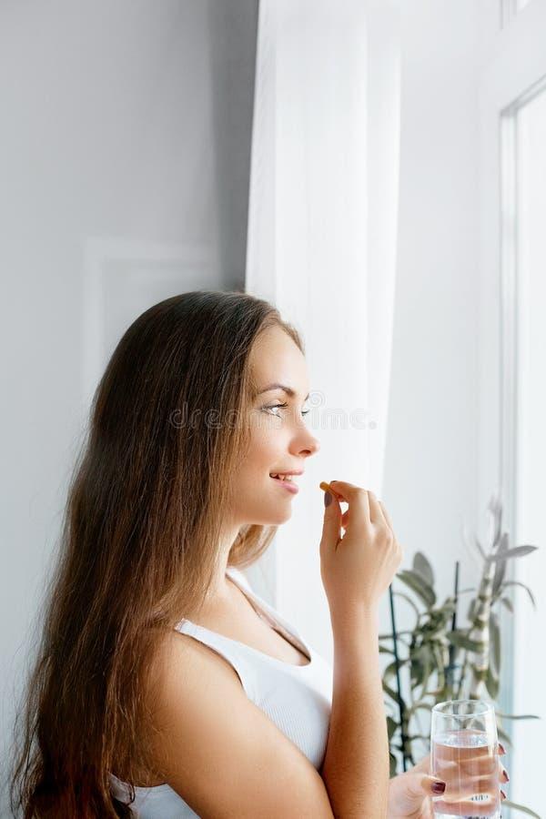 Здоровая еда, образ жизни Закройте вверх счастливой усмехаясь женщины принимая таблетку с маслом печени трески Omega-3 стоковое фото