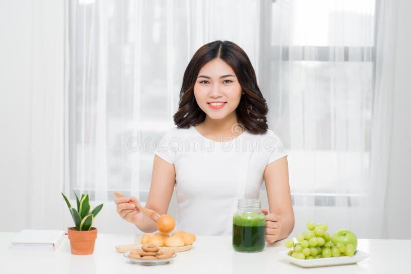 здоровая еда Счастливая красивая усмехаясь женщина выпивая зеленый вытрезвитель стоковое фото