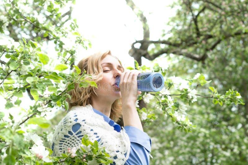 Здоровая женщина выпивает сад воды весной стоковая фотография