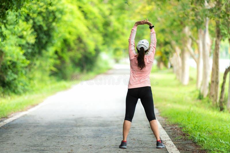 Здоровая женщина нагревая протягивающ ее оружия Азиатская разминка женщины бегуна перед фитнесом и jogging встреча на равенстве п стоковая фотография rf