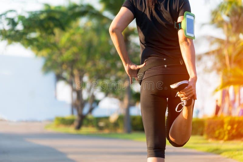 здоровая жизнь Азиатский бегун женщины фитнеса протягивая ноги перед разминкой бега внешней в парке стоковое изображение rf