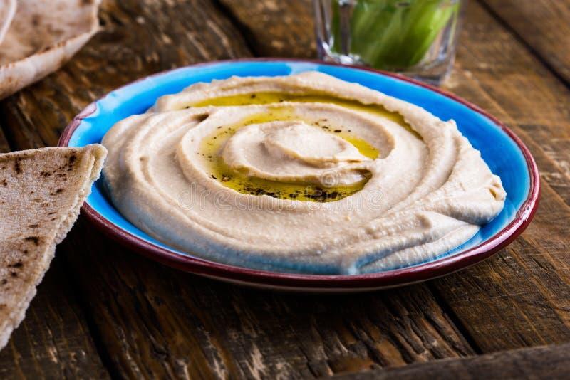 Здоровая закуска vegan, hummus с хлебом питы и ручки огурца стоковое изображение rf