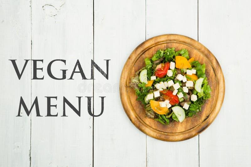 Здоровая концепция еды - салат свежего овоща с меню Vegan растительности, тофу, томатов, огурца и текста стоковые фото