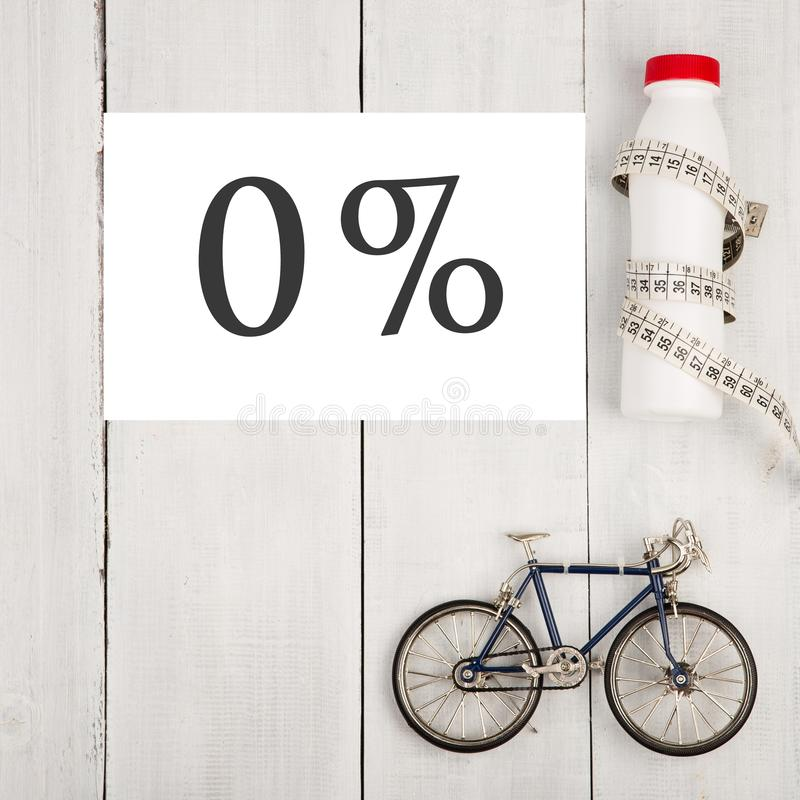 Здоровая концепция образа жизни, спорт и диета - модель велосипеда, бутылка воды, лента сантиметра и проценты текста 0% стоковое изображение rf