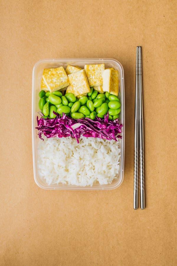 Здоровая коробка бенто vegan азиатск-стиля с рисом, зажаренным тофу, фасолями edamame и красной капустой и палочками металла на с стоковая фотография rf