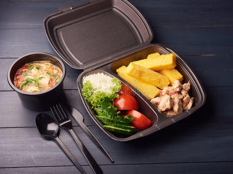 Здоровая коробка для завтрака с сандвичем и свежими овощами и супом на черной деревянной предпосылке стоковые изображения rf