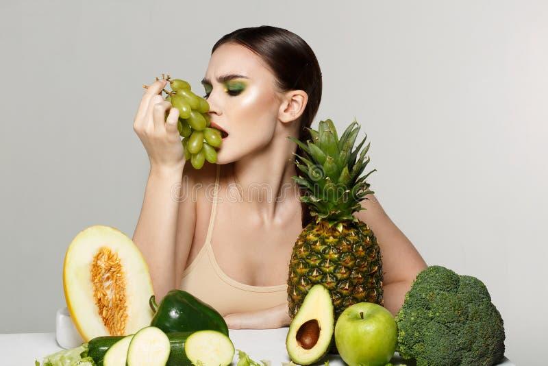 Здоровая красивая девушка брюнета с ярким макияжем искусства есть виноградины стоковая фотография rf