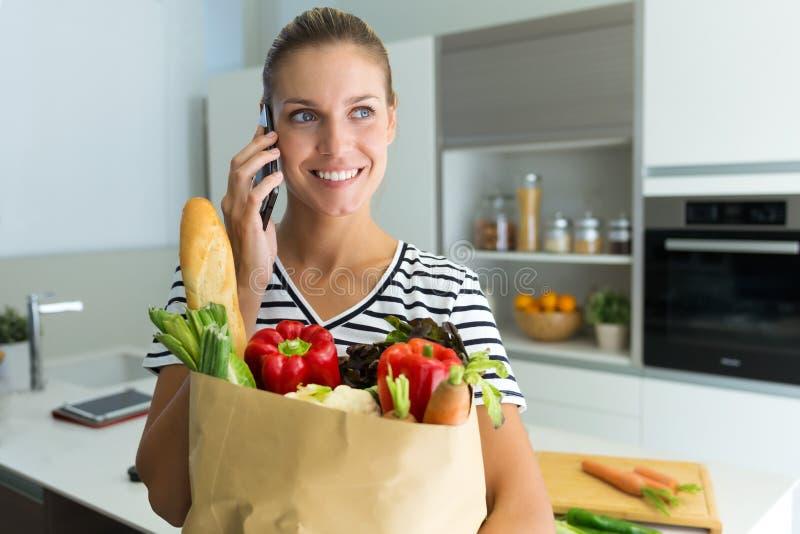Здоровая молодая женщина разговаривая с ее телефоном пока держащ овощи в продуктовой сумке в кухне дома стоковые фото