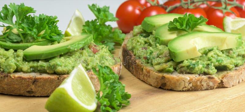 Здоровое блюдо - сандвичи гуакамоле на крупном плане деревянной доски стоковая фотография