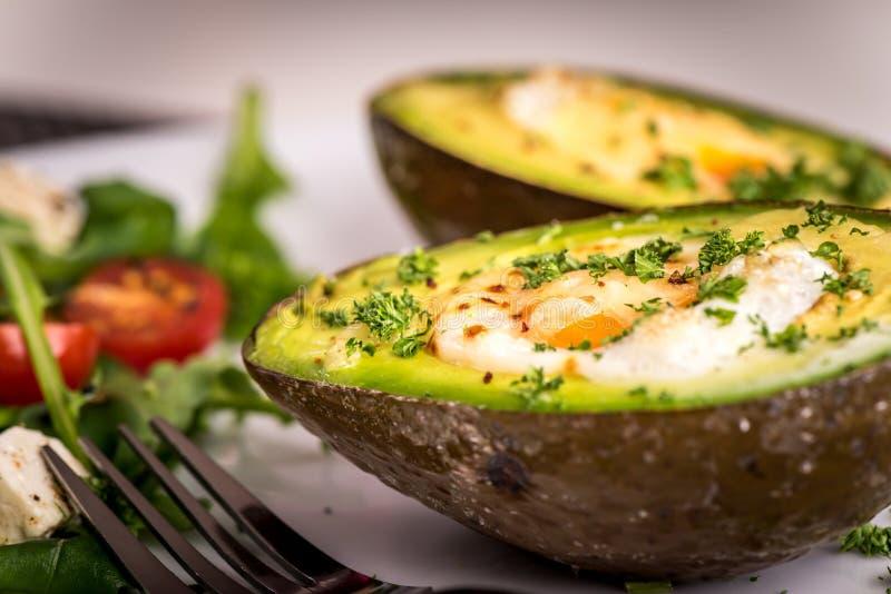 Здоровое блюдо vegan - авокадо испек с яичком и салатом с rucola стоковые фотографии rf
