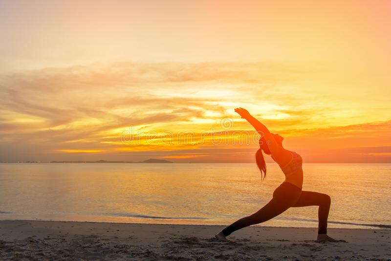 Здоровое хорошее Силуэт женщины образа жизни йоги раздумья на заходе солнца моря стоковые фотографии rf