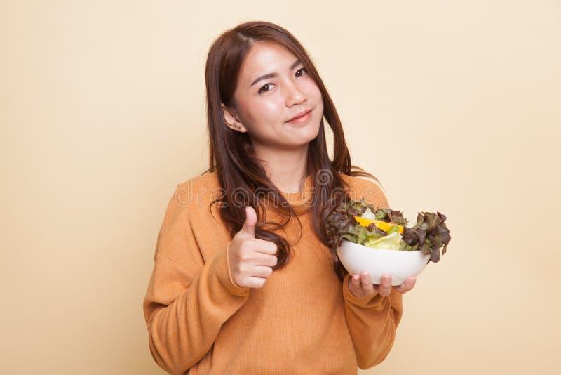 Здоровые азиатские большие пальцы руки женщины вверх с салатом стоковое фото rf