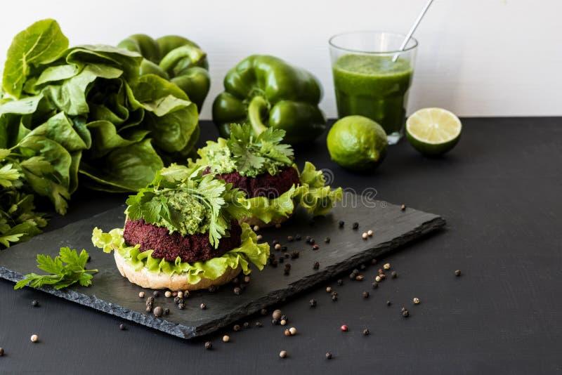 Здоровые бургеры фаст-фуда vegan с котлетой свеклы на черной предпосылке стоковая фотография rf